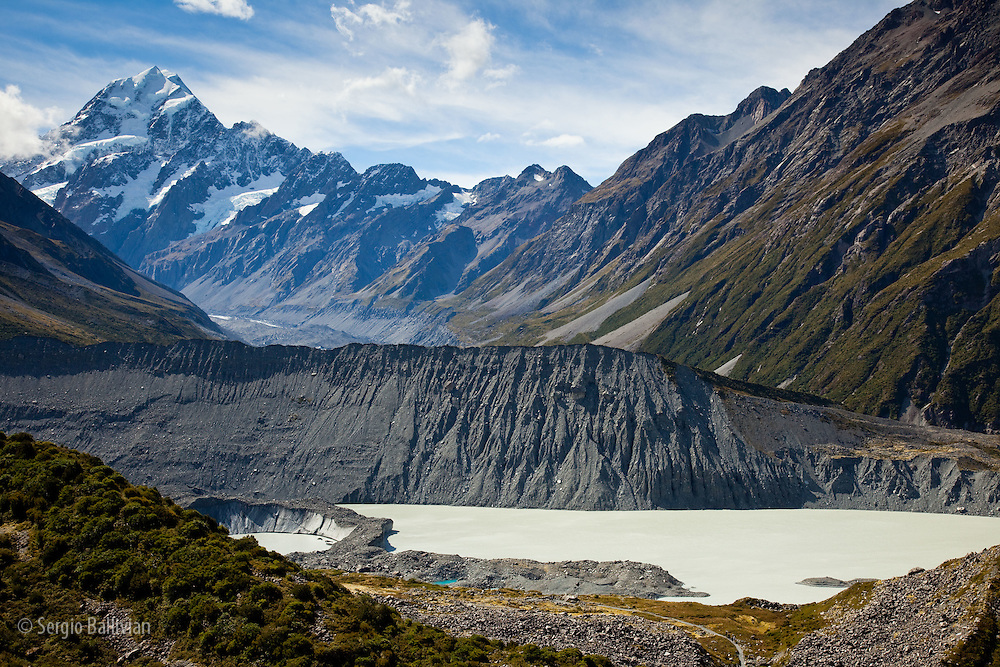 Early morning sun  lights the summit of Aoraki / Mt. Cook and the Hooker Glacier in New Zealand's Southern Alps in Aoraki/Mt. Cook National Park in the South Island.  The rugged landscape has been carved by glaciers, wind, water and tectonic shifts over millenia thus providing a challenging  playground for people seeking adventures from all over the world.