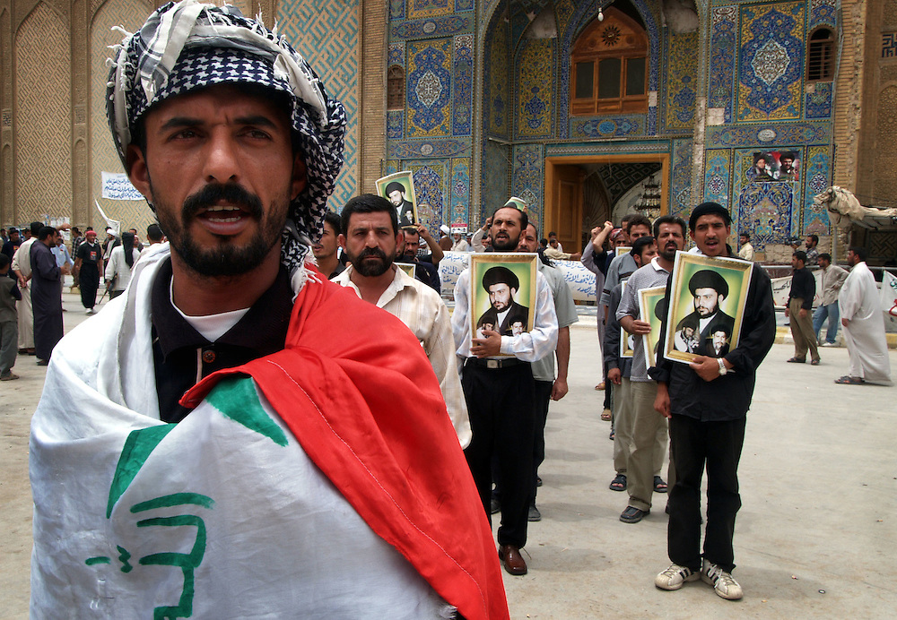 27 May 2004..Najaf, Iraq...Deal in Najaf...For the first time in weeks the main road between Kufa and Najaf is virtually void of Mehdi army foot soldiers. ..Moqtada al-Sadr the firebrand cleric with popular support in Najf, Kufa and Sadr city, a poor and violent suburb of Baghdad, has agreed in a deal with US forces to stand down his private militia who have been exchanging fire on the edges of the city for many weeks. al-Sadr says his force will disarm on the understanding that US forces do not enter the holy city...On the streets around Najaf's mosque Mehdi army fighters made a final parade but in the background some fighters retained their weapons and the militia are still maintaining some of their firing positions in the expectation that the US forces will not honour the deal.