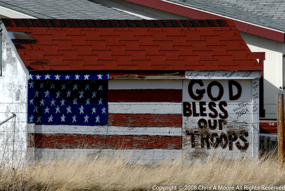 "Driving along I-90 near Big Timber, Montana my wife spotted this building.  The owner had painted an American Flag with God Bless Our Troops on the side.  If one looks closely you can see the names of area residents that are serving in our Armed Forces painted on as well. ""and President Bush."""
