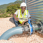 CAPTION: Naison inspects a pipe at the reservoir of the Kufandada River Protection and Irrigation Scheme Project. LOCATION: Bikita District, Masvingo Province, Zimbabwe. INDIVIDUAL(S) PHOTOGRAPHED: Naison Chingwe.