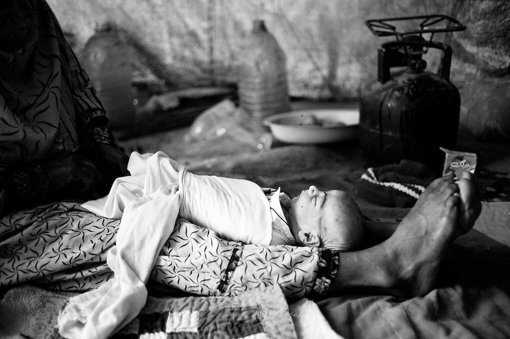 After completing all the different steps in the traditional naming ceremony, the baby gets wrapped into a white cloth. Hamida's mother performed this ceremony in the tent where the family now lives after having been displaced for over two months since flood waters destroyed their house. Karachi, Pakistan, 2010
