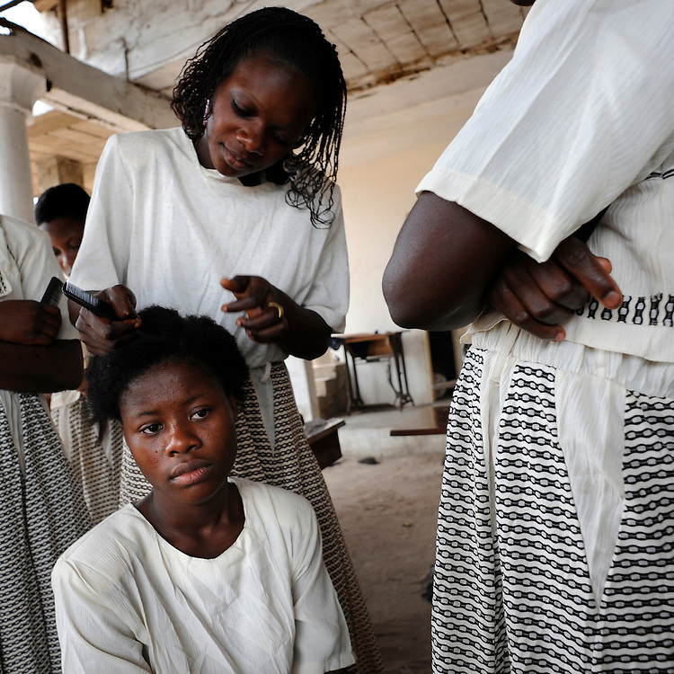 Young african girl prepares to cut a customers hair with scissors and comb in hand in Cotonou, Benin March 1, 2008.