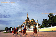 A group of Buddhist monks cross the plaza fronting the grounds of The Royal Palace temple complex in Phnom Penh, Cambodia.