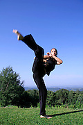 high kick - attractive young woman practicing self defense