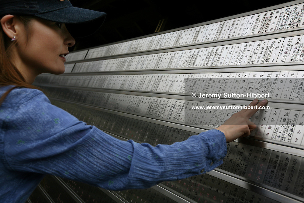 Shoko Tendo touches the names of her two dead parents (father Hiroyasu Tendo and mother Satomi Tendo) on a memorial wall in the Hitennotsuka cemetery, in Sugamo district of Tokyo, Japan, Friday, Aug. 31st, 2007. Shoko Tendo, daughter of Yakuza boss Hiroyasu Tendo,(now deceased), has written an autobiographical book - 'Yakuza Moon',  describing her life growing up with a Yakuza criminal boss for a father, of her addiction to drugs, and the failed, and often violent sexual relationships she had with men. Shoko Tendo lives in Tokyo with her 2 year old daughter Komachi.