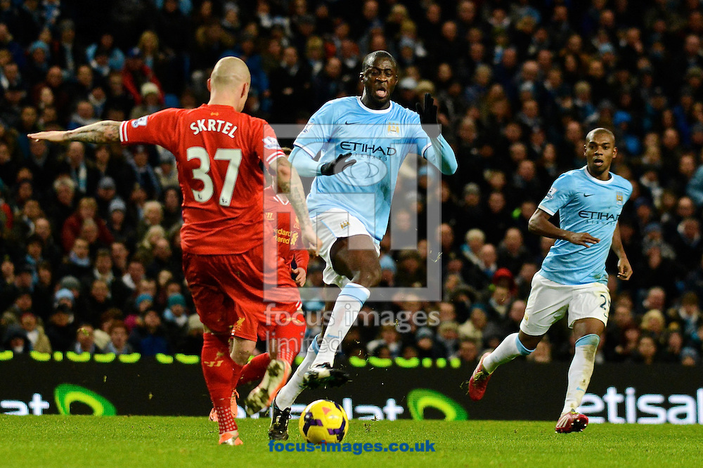 Picture by Ian Wadkins/Focus Images Ltd +44 7877 568959<br /> 26/12/2013<br /> Martin &Scaron;krteľ of Liverpool clears under pressure from Yaya Tour&eacute; of Manchester City during the Barclays Premier League match at the Etihad Stadium, Manchester.