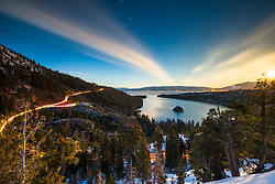 """Emerald Bay at Night 1"" - Photograph of Emerald Bay taken at night, the moon is rising on the right and the lights from cars can be seen on the left."