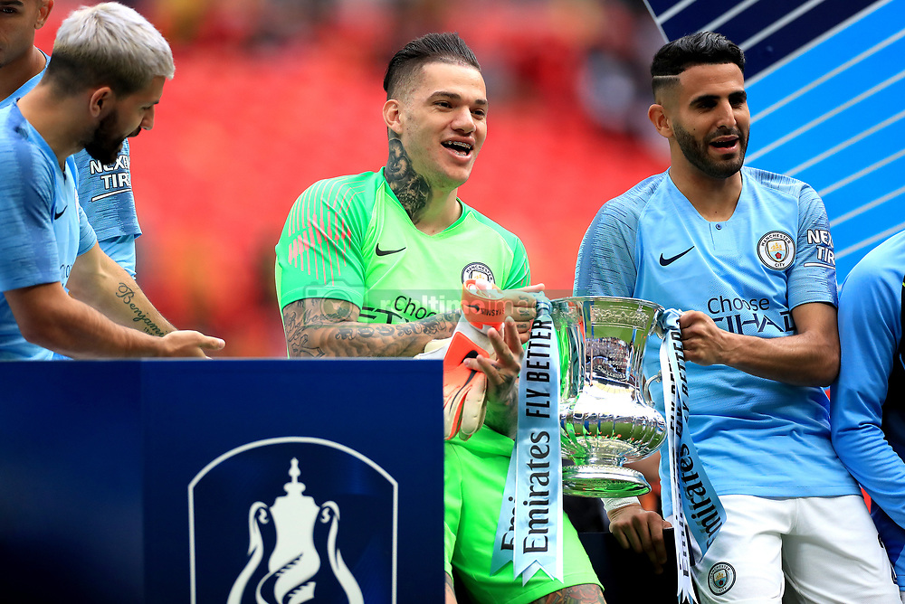 Manchester City's Ederson (left) and Riyad Mahrez (right) celebrates with the trophy after winning the FA Cup Final at Wembley Stadium, London.