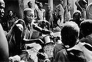 A man distributes donated  grain at a refugee distribution site in Wau, Sudan.1989