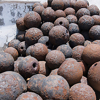 A pile of rusted cannonballs at the Cape Coast Castle, a UNESCO World Heritage Site located along the Gold Coast of Ghana.