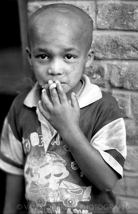 An orphan child smokes a cigarette to show off his attitude.