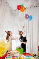 Brother and sister catching helium party balloon
