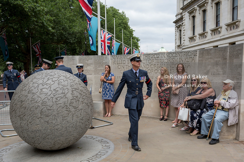 On the 100th anniversary of the Royal Air Force (RAF) and following a flypast of 100 aircraft formations representing Britain's air defence history which flew over central London, a serviceman leaves Horseguards, passing the memorial to those killed in the 2002 Bali bombing, on 10th July 2018, in London, England.