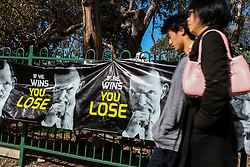 © Licensed to London News Pictures. 7/9/2013. Australian voters walk past anti Liberal party campaign posters in the electorate of Chisolm during the Australian Federal Election. Photo credit : Asanka Brendon Ratnayake/LNP
