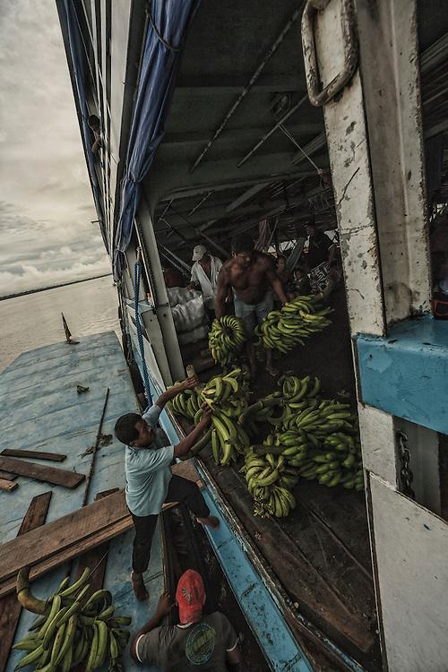 Brazil, Amazonas, rio Amazonas. Un producteur de bananes s'ammarre au passge d'un bateau pour livrer sa recolte qui sera transportee et vendue a Manaus.
