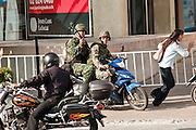 14 MAY 2010 - BANGKOK, THAILAND: Soldiers on a motorcycle take evasive action as pedestrians scatter after Red Shirts fired rockets at the troops at the intersection of Rama IV and Witthayu Roads in Bangkok Friday morning. Tensions among Red Shirt protesters demanding the dissolution of the current Thai government rose overnight after Seh Daeng, the Red Shirt's unofficial military leader was shot in the head by a sniper. Gangs of Red Shirts have taken over military checkpoints on Rama IV and are firing small rockets at military helicopters and army patrols in the area. Troops have responded by firing towards posters.  PHOTO BY JACK KURTZ