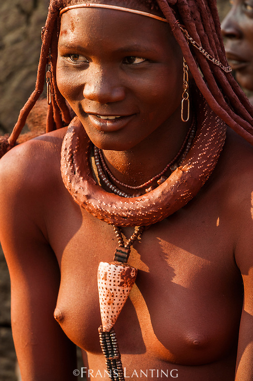 Young Himba woman wearing conch shell and other adornments , Kaokoland, Namibia