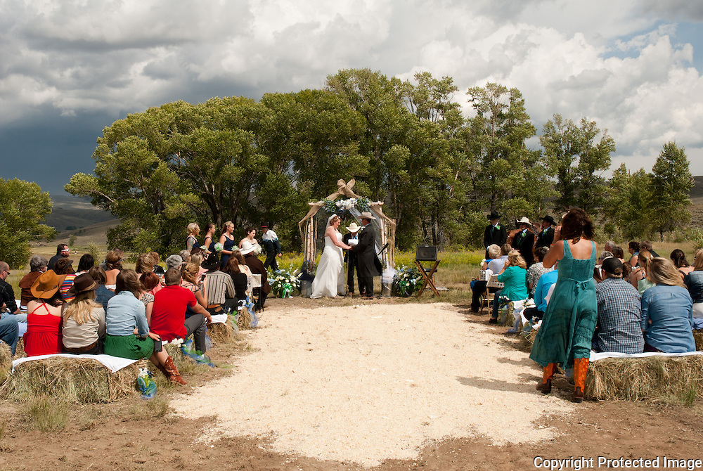 This beautiful wedding took place just outside of Parshall, CO.  The groom rode in on horseback with all his groomsmen following.  The bride and her gals rode up in the back of a truck.  The ceremony took place overlooking fields of fresh cut hay and with mountains in the background and heavy storm clouds moving in.  Their love for their family, friends and animals were evident at this cowboy wedding.