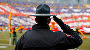 A police officer salutes a tribute to veterans prior to the start of the Green Bay Packers Arizona Cardinals NFL football game Sunday, Nov. 4, 2012, in Green Bay, Wis. (AP Photo/Tom Lynn)