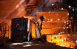 SERAING, BELGIUM - APRIL-23-2005 - An iron worker dressed in protective clothing manipulates molten iron ore in a blast furnace. (Photo © Jock Fistick)