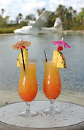 Two alcoholic drinks sit on a table on the beach of a lake at the Royal Pacific Resort at the Universal Orlando Resort in Orlando, Florida.