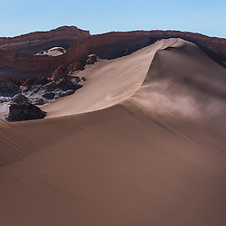 The wind blows over the top of the grand dune in Valle de la Luna, Valley of the Moon, Chile.