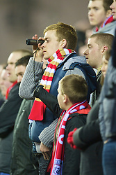 WIGAN, ENGLAND - Wednesday, January 28, 2009: Eye spy with my little eye... another two points dropped. A Liverpool supporter uses a monocular to get a closer look as Liverpool take on Wigan Athletic during the Premiership match at the JJB Stadium. (Mandatory credit: David Rawcliffe/Propaganda)