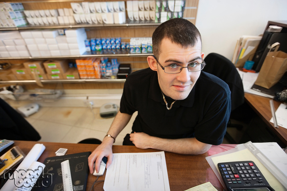 Portrait of a happy lighting shop owner sitting at desk in store