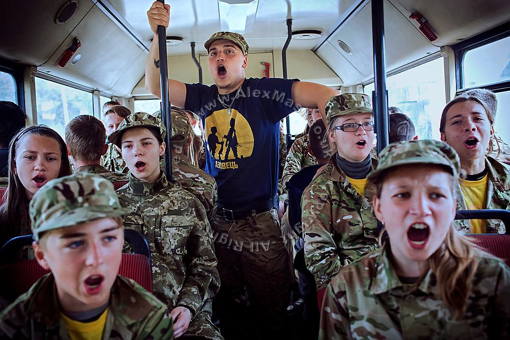 A group of youngsters participating to the nationalist Azovets children's camp are chanting patriotic Ukrainian songs while travelling on their bus to a former tank factory, now functioning as training base and repairs workshop near the village of Buzova, 30 km west of Kiev, the capital of Ukraine.