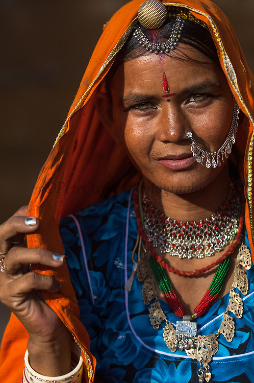 Woman wearing their traditional sarees and silver jewellery. Jaisalmer. Rajasthan, INDIA<br /> Heavy ankle bracelets are common as well as nose rings and silver bangles.<br /> Founded in 1156 Jaisalmer grew to be a major staging post on the trade route across the forbidding Thar desert from India to the west. It is known as the Golden City as the fort and town's buildings are built from the local yellow sandstone. The bustling narrow streets are lined with tradesmen selling their wares. Many of the smalll shops are occupied by descendents of the original owners. There are many exceptional Havelis (mansions of rich merchants - exquistely carved) both in the fort and the old walled town.