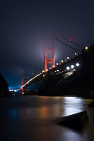 The fog touched Golden Gate Bridge in San Francisco, USA, as seen from the Fort Baker side of the bay. The needles are the rocks in the foreground, surrounded by the flat reflections of the dark night time waters