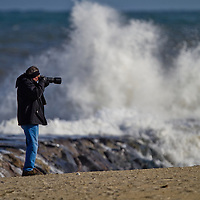 A photographer takes photos of large waves crashing into a rock (jetty) in Asbury Park NJ.   A persistent east wind cause seas to 10 feet at the shoreline.