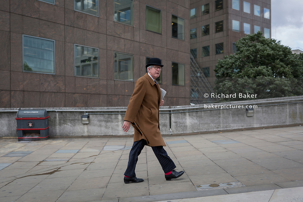 A city gent wearing red socks and a traditional but now a very rarely-seen bowler hat walks towards London Bridge rail station, on 6th June 2017, on London Bridge, in the south London borough of Southwark, England. The griffin behind him is on the southern end of the Thames crossing but marks the southern boundary of the City of London, the capital's financial district.