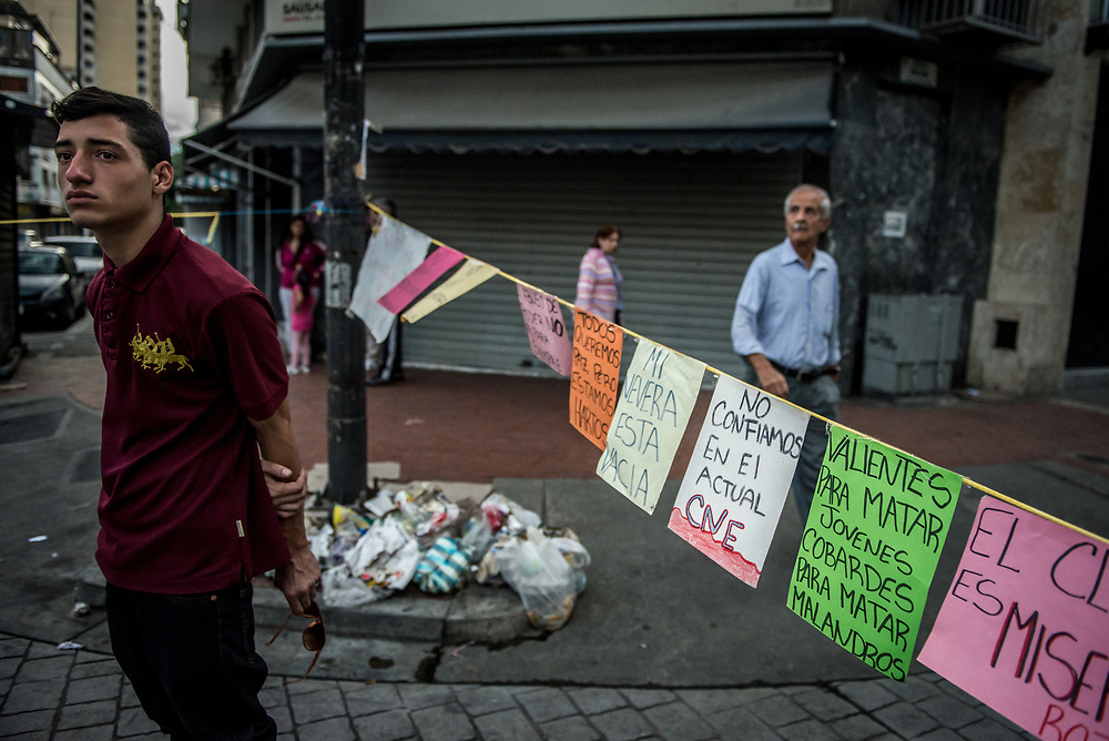 """CARACAS, VENEZUELA - JULY 27, 2017: A road blocked by protesters, with signs that say in Spanish, """"My refridgerator is empty"""", """"We don't trust in the actual CNE"""" (National Elections Council) blocked in support of a national strike, called by the political opposition to last for  48 hours, all day July 26th and 27th. They called for their supporters to close businesses, not go to work, and instead create barricades to block off their streets.  Opposition controlled areas of the country were completely shut down.  The strike was called as part of the opposition's civil resistance movement - that began on April 1st, to protest against the Socialist government's attempt to elect a new constituent assembly that will have the power to re-write the constitution, and will threaten democracy.  PHOTO: Meridith Kohut for The New York Times"""