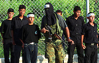 An instructor looks over recruits at a training camp for the Al-Aqsa Martyrs Brigade in Gaza City. The group, which emerged shortly after the outbreak of the current Palestinian intifada, has carried out operations against Israeli soldiers and settlers in the West Bank and Gaza, and suicide attacks on civilians inside Israel. In March 2002, after a deadly al-Aqsa suicide bombing in Jerusalem, the U.S. State Department added the group to the U.S. list of foreign terrorist organizations. (Photo/Scott Dalton)