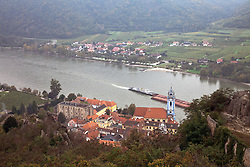 Wachau Valley, Austria: A barge passes Durnstein on its way up the Danube towards Melk.  Durnstein retains its historic character and air of romance, one of the most popular stops on the Danube on a cruise between Melk and Durnstein.  The Castle-ruin Durnstein still stands on the high bluff above town.