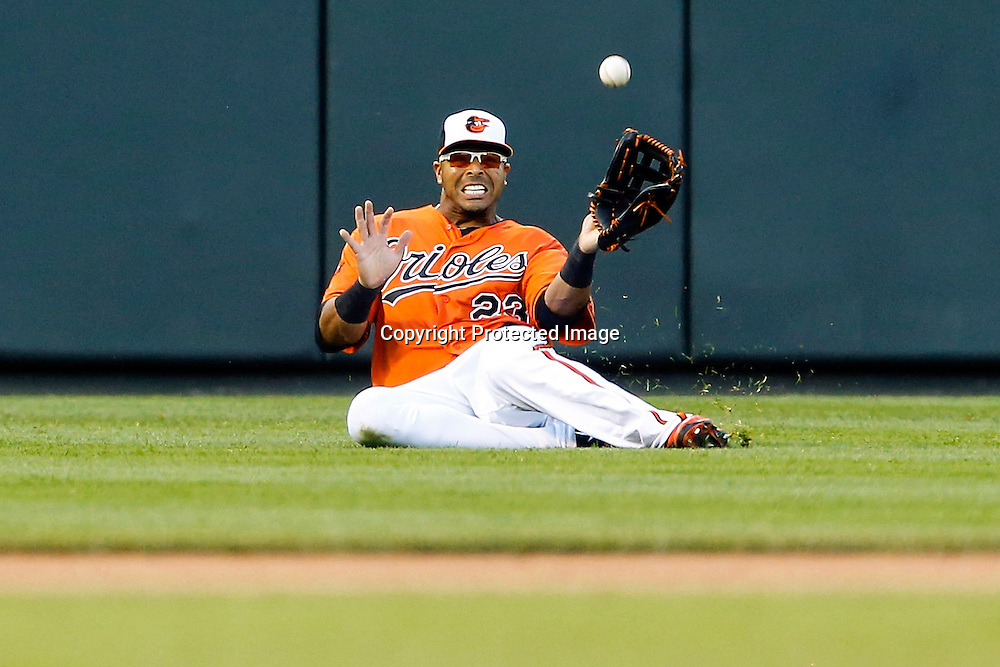 Left fielder Nelson Cruz #23 of the Baltimore Orioles slides and catches a shallow line drive by Josh Thole #22 of the Toronto Blue Jays for the third out in the eighth inning of the Orioles' 3-2 victory at Oriole Park at Camden Yards.