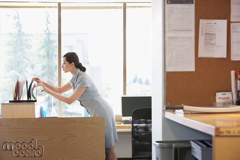 Woman checking files in office