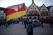 Frankfurt am Main | 30 Mar 2015<br /> <br /> Am Montag (30.03.2015) demonstrierten etwa 40 Menschen unter dem Namen &quot;Freie B&uuml;rger f&uuml;r Deutschland&quot; auf dem R&ouml;merberg in Frankfurt am Main gegen Islamisierung und zahlreiche andere &Uuml;bel, die Gruppe war zuvor unter dem Namen &quot;PEGIDA&quot; aufgetreten. Etwa 600 Menschen protestierten lautstark gegen diese Kundgebung.<br /> Hier: &quot;Freie B&uuml;rger f&uuml;r Deutschland&quot;-Demonstrant (Demonstrantin?) mit einer Deutschland-Fahne vor dem R&ouml;mer.<br /> <br /> &copy;peter-juelich.com<br /> <br /> [No Model Release | No Property Release]