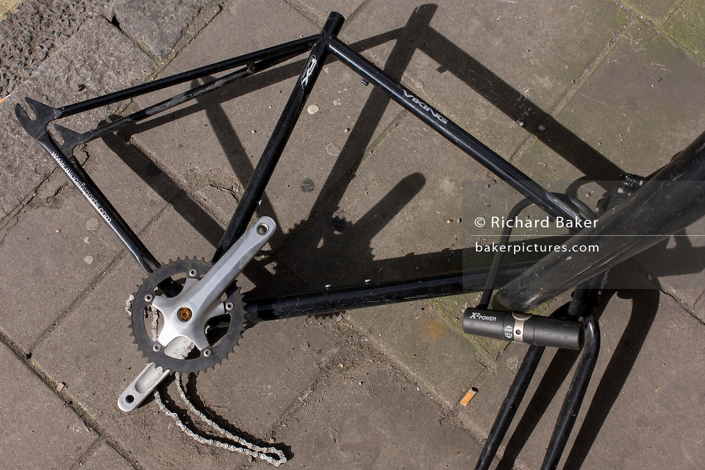 Vandalised and stripped bike frame lying on a central London street pavement.