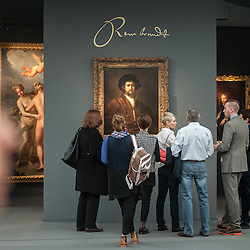 London, UK - 15 October 2014: people looks at 'Portrait of a Man with Arms Akimbo by Rembrandt at the Otto Naumann gallery stand during the first day of Frieze Art Fair and Frieze Masters in Regent's Park.