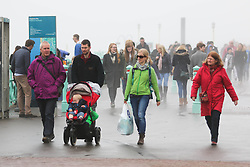 © Licensed to London News Pictures. 03/04/2015. Brighton, UK. People visiting Brighton Beach on the Good Friday Bank Holiday despite the wet weather and fog covering most of the Seaside resort and the South Coast. Photo credit : Hugo Michiels/LNP