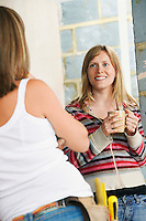 Woman with toolbelt leaning against wall talking to friend