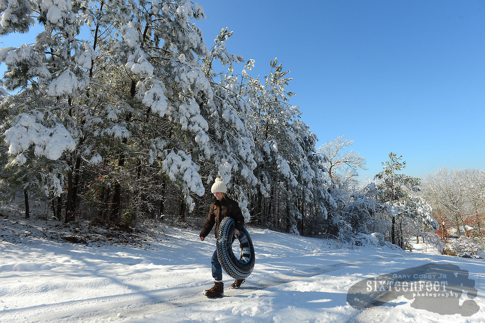 Gary Cosby Jr./Decatur Daily   Snow blankets the Tennessee Valley Thursday morning after a snow that began late Wednesday and fell through much of the night.  Paula Burleson walks up Colony Lane in Hartselle as she tubes and sleds with her family and friends.