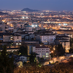 Bergamo, Italy - Aerial view of the old medieval city (Città Alta) illuminated at night seen from San Vigilio hill.