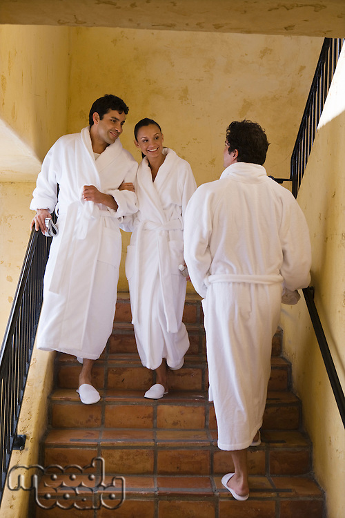 People in bathrobes, talking on stairs