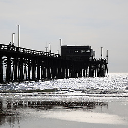 Newport Pier on Balboa Peninsula in Newport Beach Orange County Southern California. Newport Pier is a popular Newport Beach attraction and has a restaurant at the end.