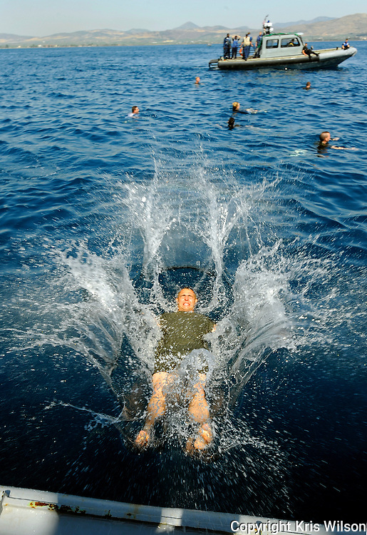 A Marine assigned to the 22nd Marine Expeditionary Unit (22 MEU) plunges into the Aegean waters from the stern gate of the amphibious dock landing ship USS Fort McHenry (LSD 43) during an all hands swim call off the coast of Volos, Greece. USS Fort McHenry is currently on a scheduled deployment with the Bataan Amphibious Readiness Group (ARG) in support of maritime security operations in the U.S. 5th and 6th Fleet areas of responsibility.