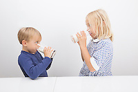 Children drinking milk while looking at each other