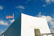 Close up picture of the USS Arizona Memorial and an American flag.